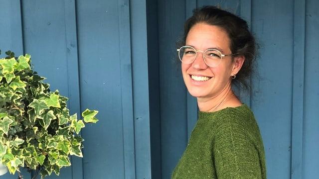 Eliane steht in vor einer blauen Wand und lächelt