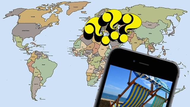 Ein Smartphone mit Fragezeichen vor einer Weltkarte.