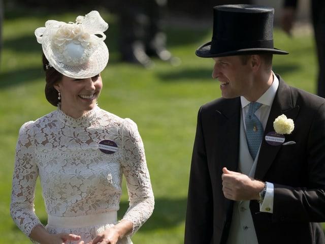 Herzogin Catherine und Prinz William sprechen miteinander. Sie trägt ein weisses Spitzenkleid mit einem Hütchen. Er Zylinder und Frack.