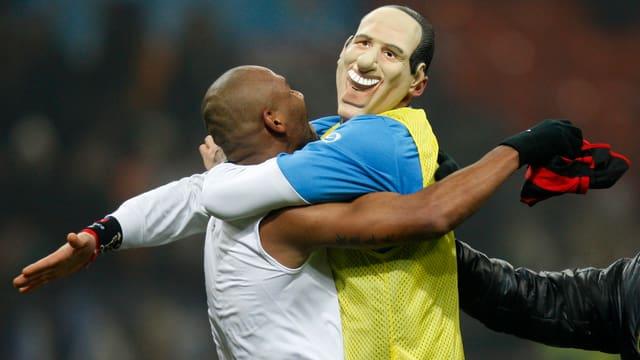 Maicon umarmt Marco Materazzi, welcher eine Berlusconi-Maske trägt.