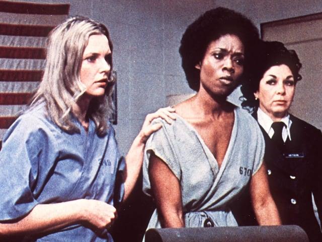 Zwei Frauen im Häftlingsanzug, daneben eine Frau in Uniform.