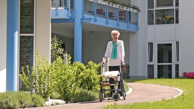 Frau mit Rollator vor Altersheim