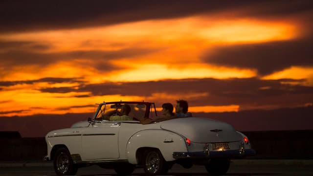 Symbolbild: Ein weisses Oldtimer-Cabriolet fährt im Licht der untergehenden Sonne auf Kuba.