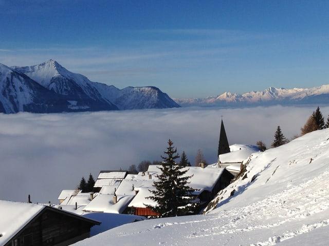 Winterliches Dorf am Berghang an der Sonne. Im Tal liegt Nebel. Darüber scheint die Sonne vom blauen Himmel.