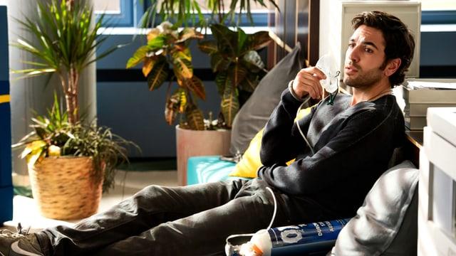 Ein junger Mann sitzt auf einem Sofa zwischen vielen Topfpflanzen und hält sich die Maske einer Sauerstofflasche ans Gesicht.