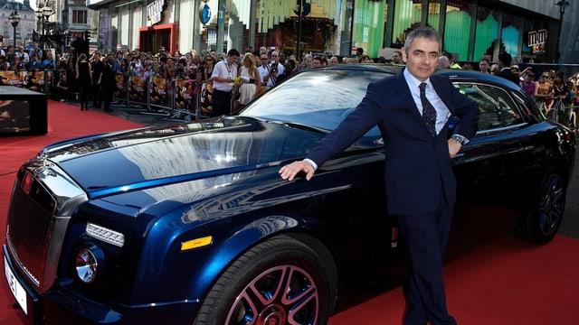 Rowan Atkinson posiert vor dem Rolls Royce.