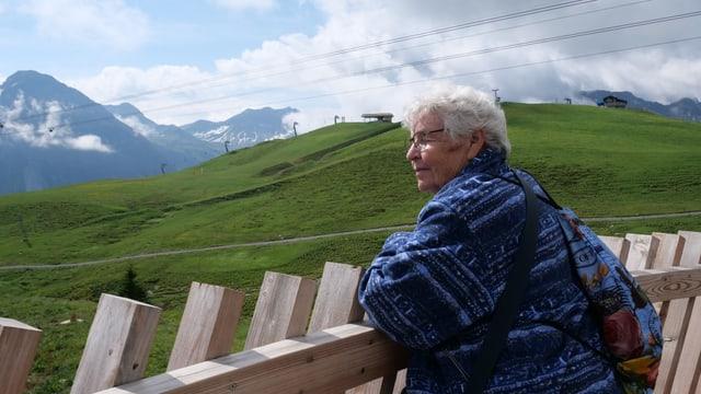 Ältere Frau steht an einem Zaun