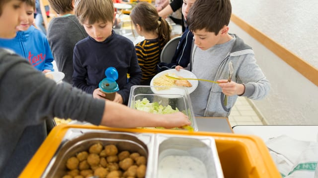 Kinder nehmen sich Essen von einem Buffet