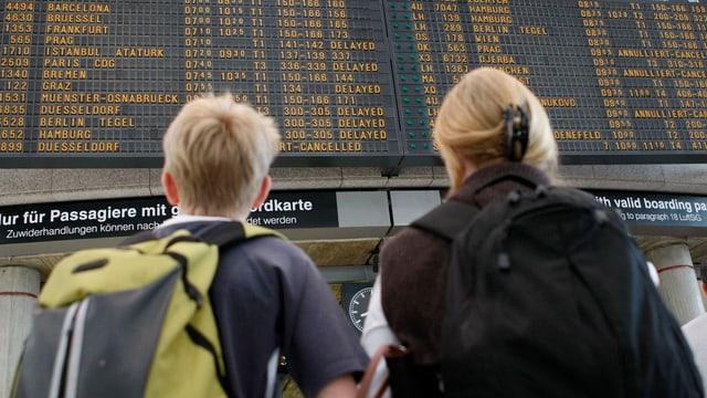 Passagiere vor einer Anzeigetafel