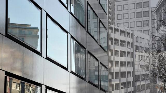 Häuser spiegeln sich in einer gläsernen Hausfassade in Genf (keystone)