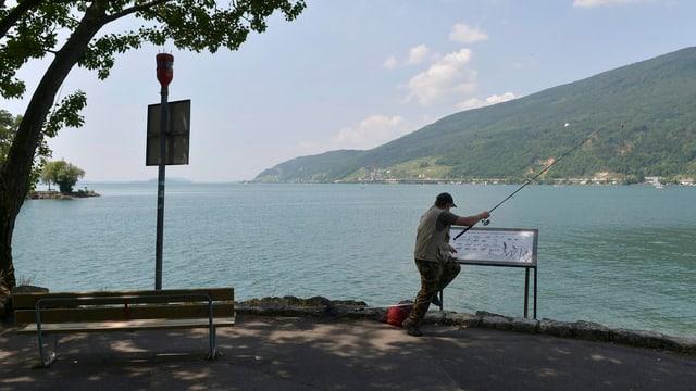 Fischer steht am Rande des Bielersees