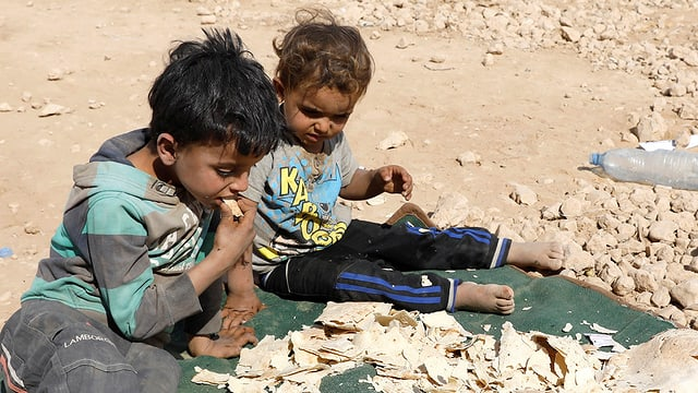 Zwei Kinder sitzen auf steinigem Boden auf einer grünen Decke, auf der Brot trocknet. Eines der Kindert kostet ein Brotstück.