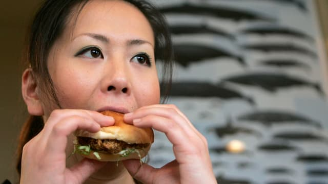 Frau isst einen Walburger.