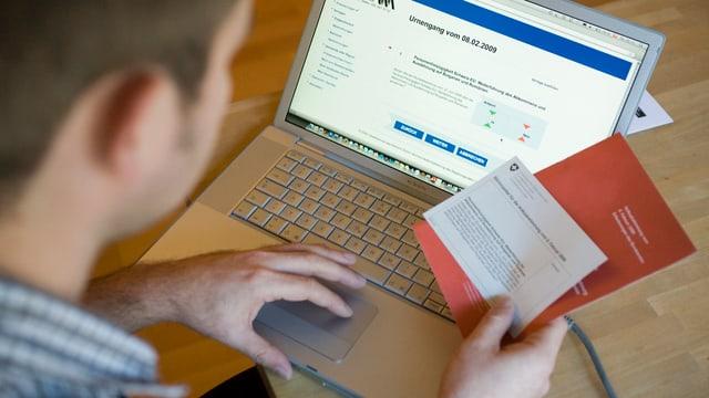 Mann vor Computer mit Abstimmungsunterlagen.