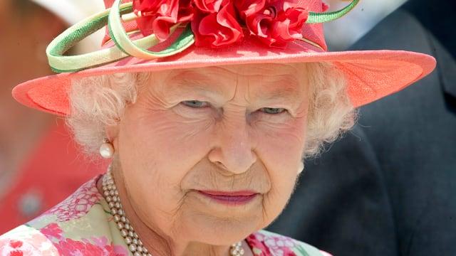 Die Queen blickt mit ernstem Blick und witzigem rosa Hut in die Kamera.