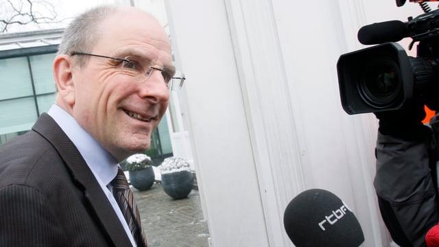 Justizminister Koen Geens seitlich vor einer Kamera, rechts unten im Bild ein Mikrofon