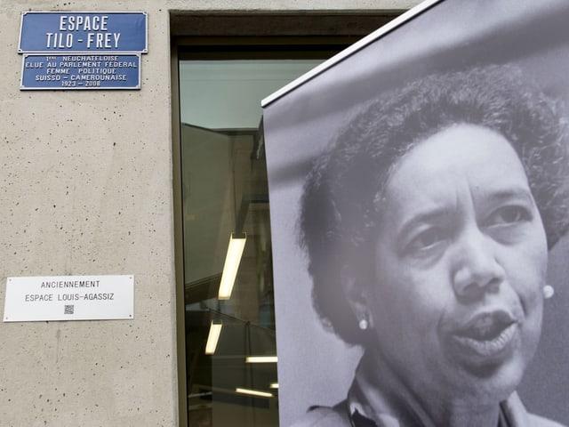 Das Bild einer schwarzen Frau neben einer Betonsäule.