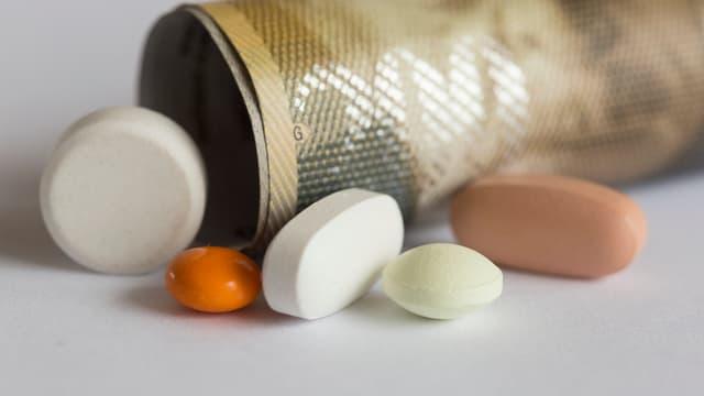 Eine gerollte 200-CHF-Note und Medikamentenpillen