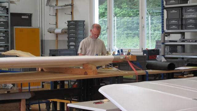 Ein Mann mit weissem T-Shirt arbeitet in einer Werkstatt an grossen weissen Flugzeugteilen.