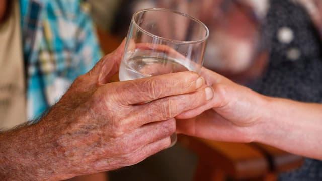 Zwei Hände an einem Wasserglas