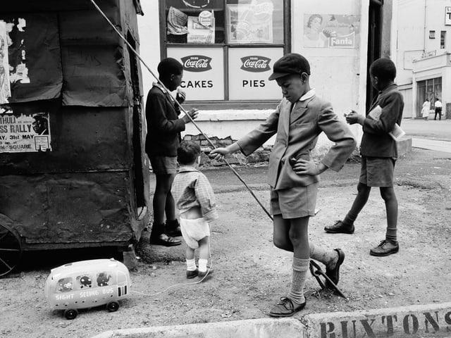 Ein schwarzer Junge spielt mit einem Spielauto und einer Angel.