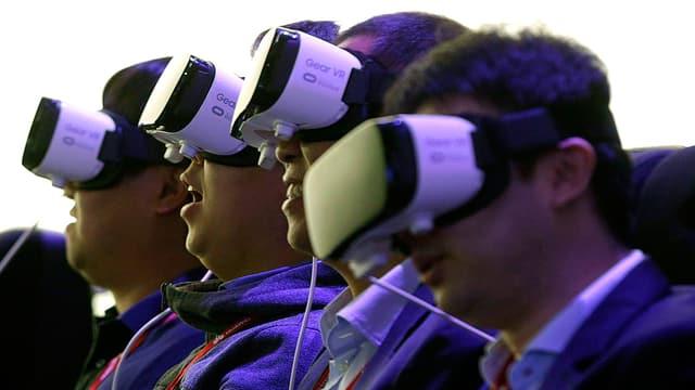 Testpersonen haben sich am «Mobile World Congress» in Barcelona eine VR-Brille von Samsung übergestreift. Sie leuchten ultraviolett.