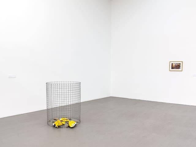 Gelbe Kartonstücke in einem Gitterbehälter, ein Bild an der Wand.