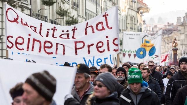 """Bauern tragen ein Transparent mit der Aufschrift """"Qualität hat seinen Preis"""" während des Umzugs der Bauerndemo in der Altstadt von Bern, (keystone)"""
