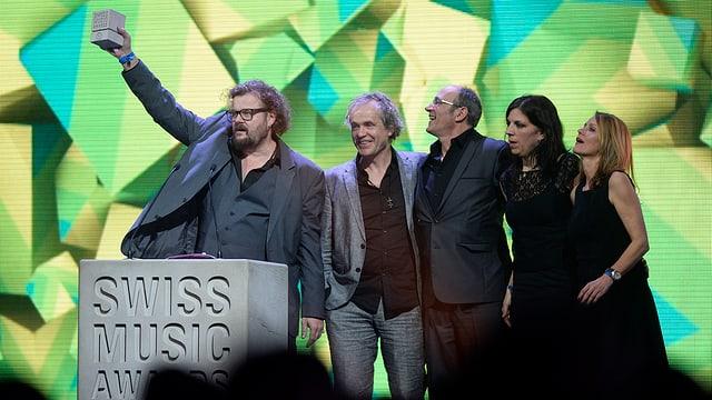 Ils 5 commembers da patent Ochsner sin la tribuna dal Swiss Music Awards. Il chantadur Kühne Huber tegna ad aut la trofea che sumeglia in pitschen bloc da betun.