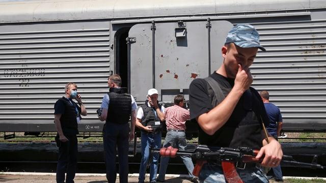 Mann mit Gewehr hält sich die Nase zu. Dahinter ist eine Gruppe Personen vor einem Eisenbahnkühlwagen zu sehen.
