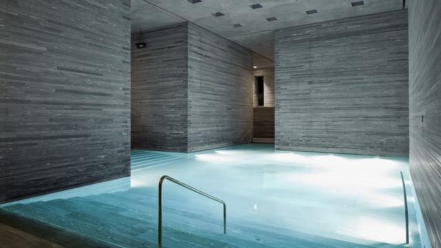 Schlichtes Thermalbad mit grauen Steinwänden und beleuchtetem Schwimmbecken