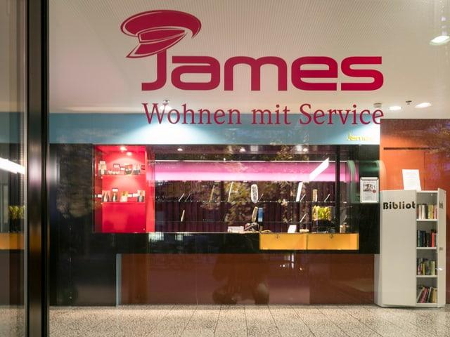 Durch ein Fenster sieht man den Empfang von «James – Wohnen mit Service».