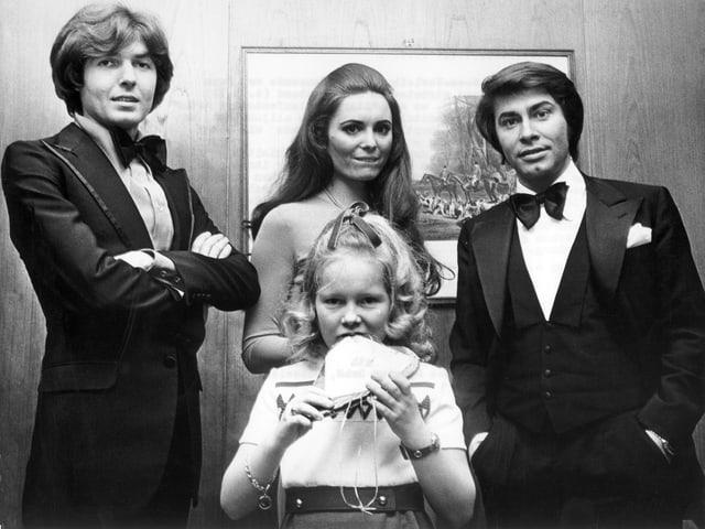 Gruppenbild mit zwei Männern, einer Frau und einem Kind in schicker Kleidung.