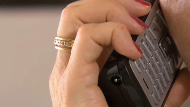 Eine Frau hält den Telefonhörer an ihr Ohr.