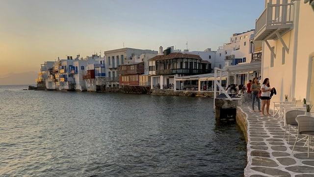 Griechisches Dorf am Meer mit Touristen.