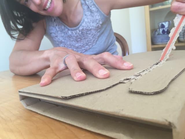 Annette König packt aus dem Karton Das Päckchen von Franz Hohler aus