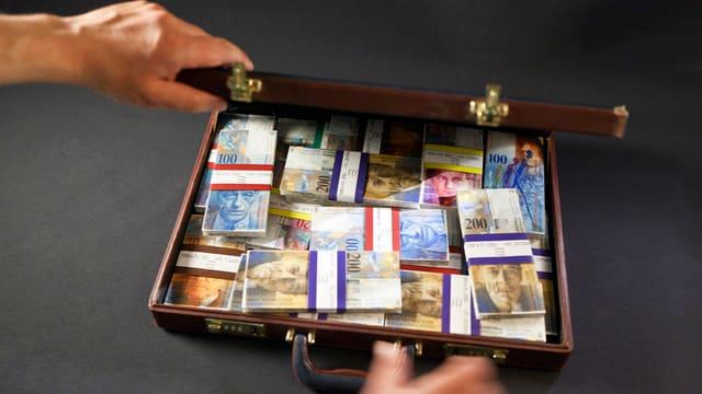Hände öffnen Koffer mit Geld