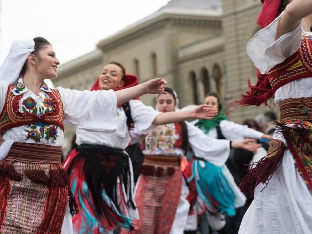 Eine Gruppe von Mädchen und jungen Frauen tanzt in bunten albanischen Folklore-Kostümen vor dem Bundeshaus.