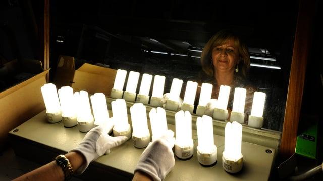 Osram-Mitarbeiterin kontrolliert Energiesparlampen auf ihre Funktionstüchtigkeit