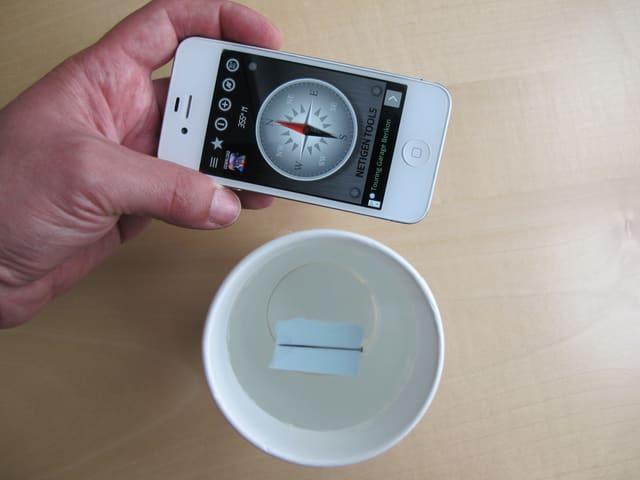 Eine Nadel schwimmt auf einem kleinen Zettelchen in einem Becher mit Wasser. Dazu hält eine Hand ein Handy, auf dem ein Kompass zu sehen ist. Nadel und Kompass zeigen in dieselbe Richtung.
