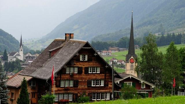 Holzhaus vor zwei Kirchen, im Hintergrund das Tal.