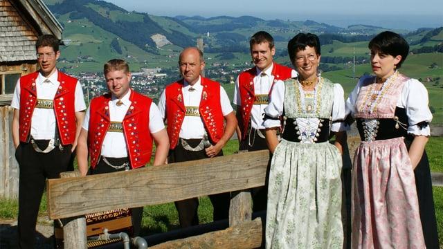 Vier Jodler und zwei Jodlerinnen in Appenzeller Trachten hinter und vor einem Holzzaun.