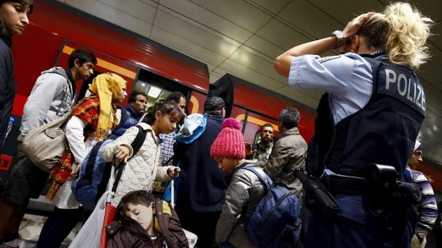 fugitivs vulan entrar en in tren, ina policista observa la situaziun