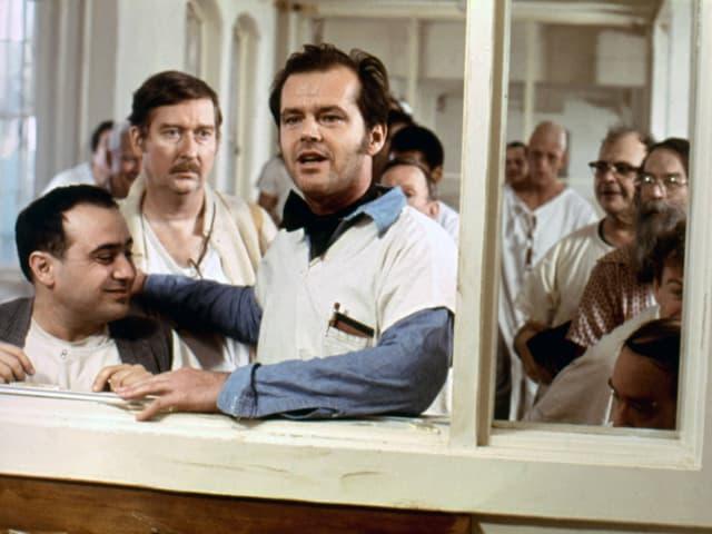 Jack Nicholson steht am Eingang zur Schwesternstation. Die anderen Patienten neben ihm.