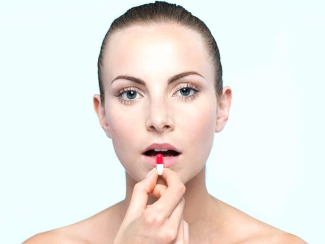 Eine Frau hat eine Tablette in der Hand und legt sie sich bald in den Mund.