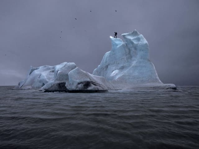 Ein Mann mit einem Bunsenbrenner steht auf auf einem Eisberg und versucht das Eis zu schmelzen.