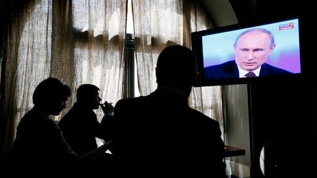 Menschen schauen auf einen Fernsehbildschirm