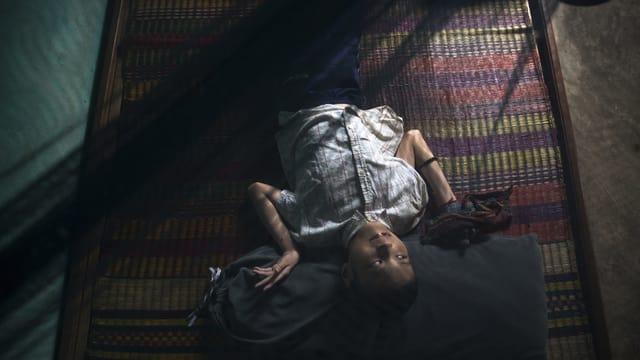 Junge liegt mit verzerrt abgewinkelten Armen und Händen auf einer Strohmatte im Halbdunkel.