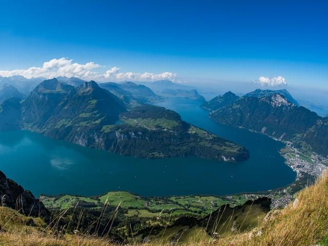 Blick von einem Gipfel auf bergige Landschaft mit Seen und kleinen Quellwolkchen über den Bergen.