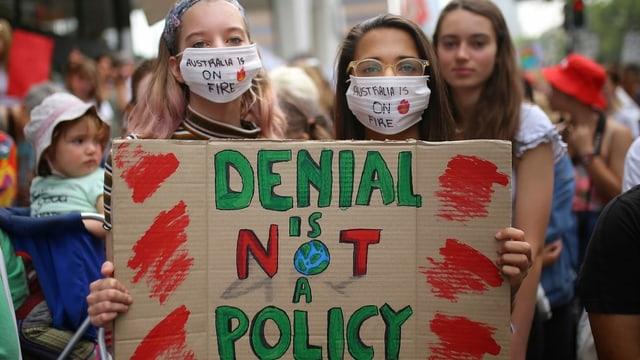 Klimademonstrantinnen mit einem Pappschild